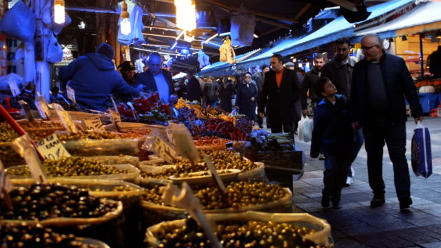 people shopping at the street market in front of olive sellers stall - turks fruit stock videos and b-roll footage