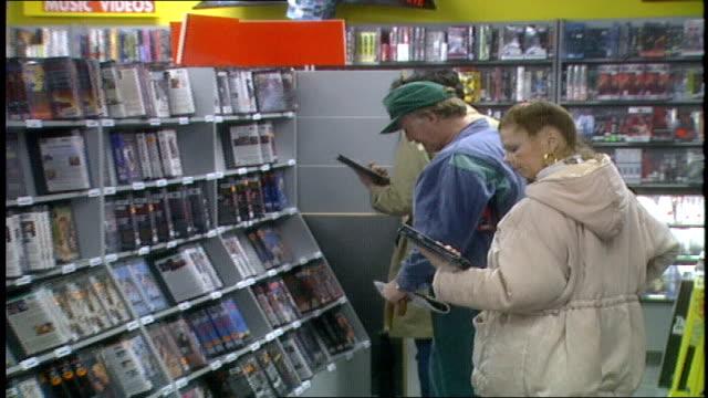 vídeos de stock, filmes e b-roll de people shopping for vhs videos - videocassete