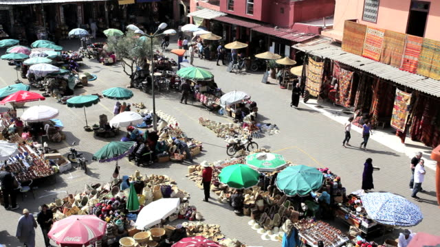 people shopping in a market square in marrakech, morocco, africa - retail occupation stock videos & royalty-free footage