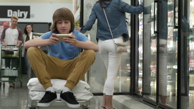 vidéos et rushes de people shopping in a warehouse supermarket - jeunes garçons