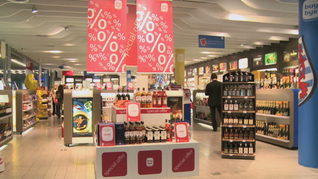ws people shopping in duty free shop / luxembourg airport, findel, luxembourg, luxembourg - bottiglia video stock e b–roll