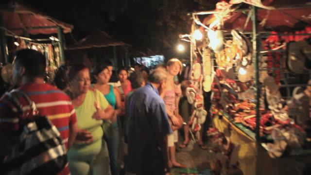 MS POV People shopping in market at night, Merida, Yucatan, Mexico