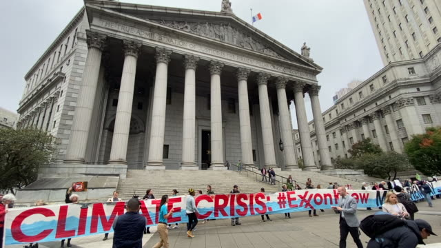 people shout slogans agains exxon as they take part in a protest against exxonmobil before the start of its trial outside the new york state supreme... - exxon stock videos & royalty-free footage