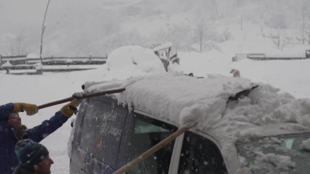 People shoveling snow off roof of van