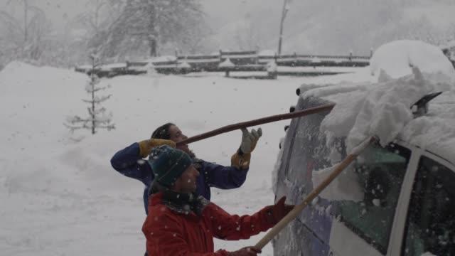 vídeos de stock e filmes b-roll de people shoveling snow off roof of van - pá para neve