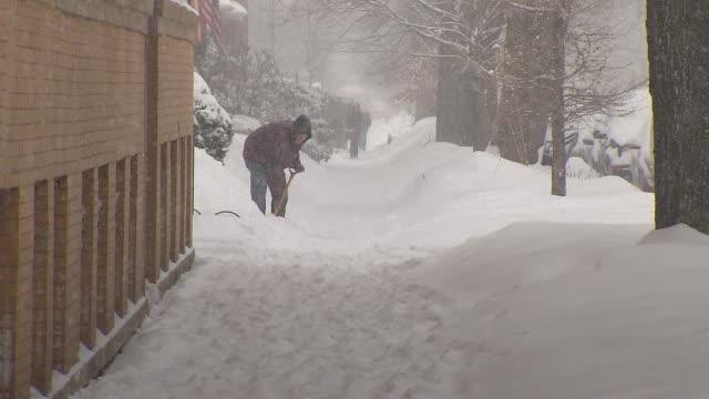 vídeos de stock e filmes b-roll de people shoveling snow off sidewalk - pá para neve