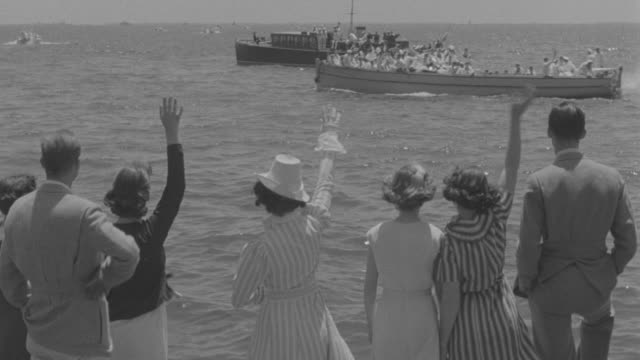 ms people showing hand to cadets in boats at sea - marinaio video stock e b–roll