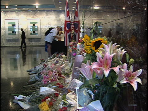 people sign the condolence book for the death of princess diana, and place flowers at the tribute in the british consulate lobby. princess diana died... - consoling stock videos & royalty-free footage