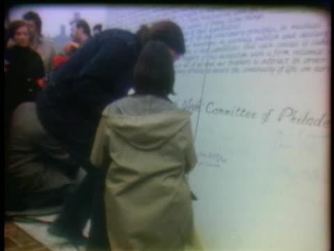 people sign their names on a giant pre-earth day poster in philadelphia, pennsylvania. - environmentalist stock videos & royalty-free footage