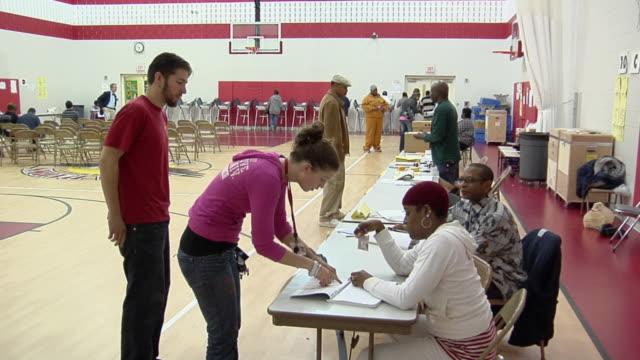 vídeos de stock, filmes e b-roll de ms, zi, zo, people signing in at registration table at polling place, toledo, ohio, usa - título de eleitor