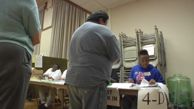 MS, People signing in at registration table at polling place, Toledo, Ohio, USA