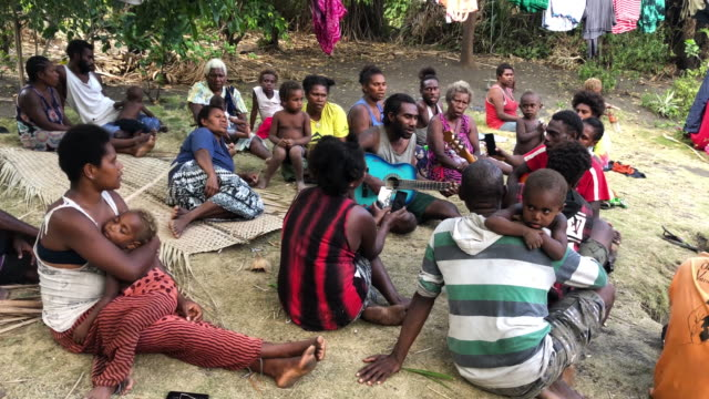 people sing in a traditional village which was wiped out by cyclone pam and rebuilt on december 03, 2019 in tanna, vanuatu. 25 percent of vanuatu's... - stillahavsöarna bildbanksvideor och videomaterial från bakom kulisserna