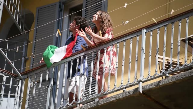 people sing on their balcony behind the italian flag during the flashmob of liberation day celebrations on april 25, 2020 in turin, italy. flashmob... - balcony stock videos & royalty-free footage