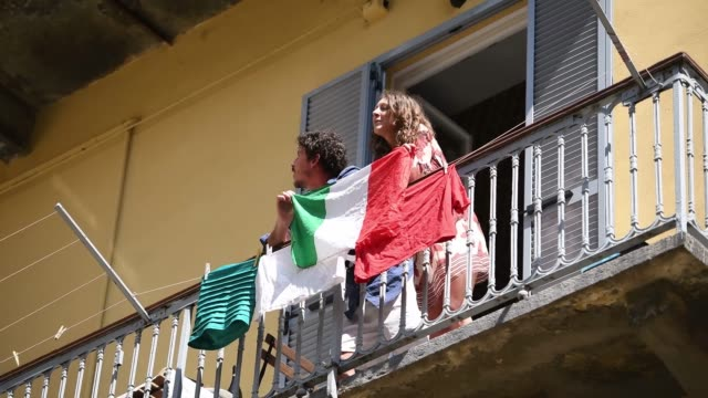 stockvideo's en b-roll-footage met people sing on their balcony behind the italian flag during the flashmob of liberation day celebrations on april 25, 2020 in turin, italy. flashmob... - balkon