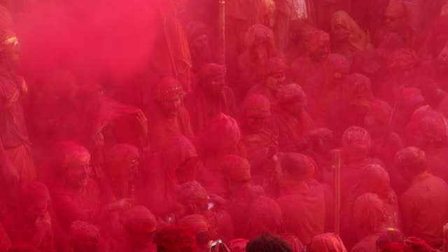 people singing folk songs at holi, festival of colour, while people throwing colors on them - religion stock-videos und b-roll-filmmaterial