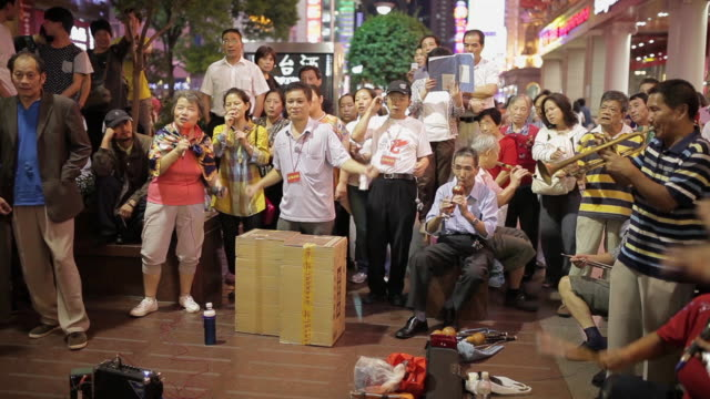 ms people singing in nanjing dong road audio / shanghai,  china - nodding head to music stock videos and b-roll footage