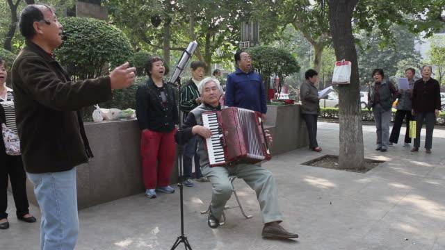 vídeos y material grabado en eventos de stock de ws people singing traditional songs in park/xian,shaanxi,china - acordeonista