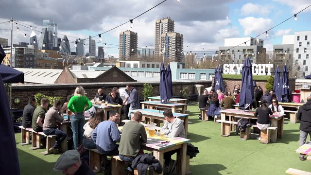 people sit and enjoy drinks and food at the skylight bar at tobacco dock, the capital's biggest outdoor rooftop bar, on april 12, 2021 in london,... - sitting stock videos & royalty-free footage