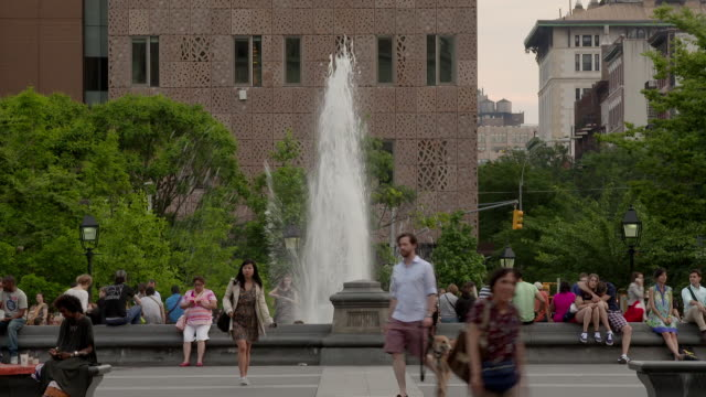 people sit and relax in washington square park by the fountain.  the nyc campus sits behind. - new york university stock videos & royalty-free footage