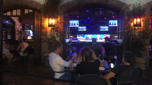 people sit and watch a broadcast of the first debate between president donald trump and democratic presidential nominee joe biden at the abbey, with... - debatte stock-videos und b-roll-filmmaterial