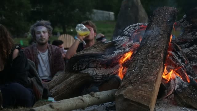 People sit around a fire at the stone circle at the Glastonbury Festival at Worthy Farm Pilton on June 27 2015 in Glastonbury England