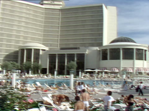 people sit at a pool to sunbath at caesars palace - zurücklehnen stock-videos und b-roll-filmmaterial