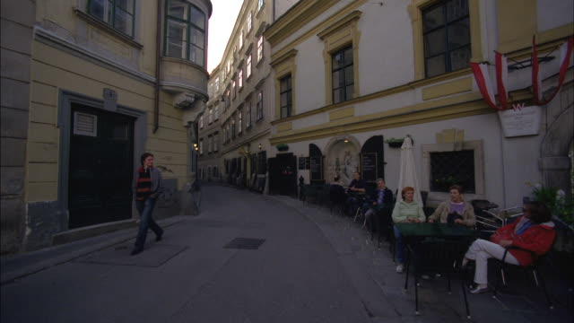 People sit at a table on a narrow street in Vienna, Austria.