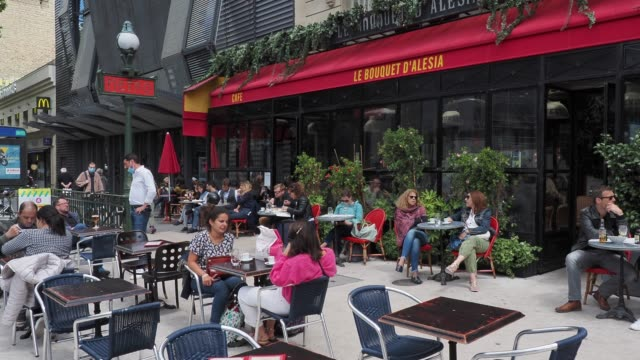 stockvideo's en b-roll-footage met people sit at a terrace in front of the alesia metro station in the 14th quarter of paris, as bars and restaurants reopen after two months of... - quarter
