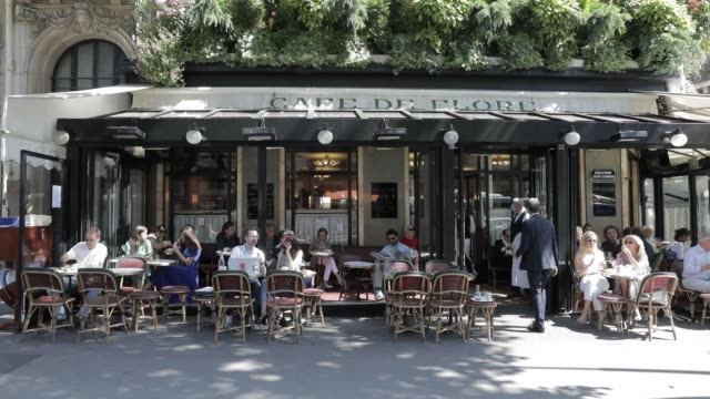 people sit at a terrace of the cafe de flore, as the lockdown restrictions ease during the coronavirus pandemic on june 2, 2020 in paris, france.... - building terrace stock videos & royalty-free footage