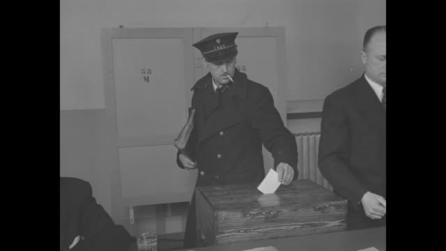 vidéos et rushes de people sit at table in room others stand in line to place ballot in box woman places ballot in box as belgians vote on whether king leopold iii... - belgique
