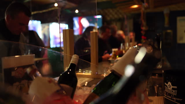 people sit at tables in a bar while plexiglass separates areas in the bar during the coronavirus pandemic on october 16, 2020 in zurich, switzerland.... - party social event bildbanksvideor och videomaterial från bakom kulisserna