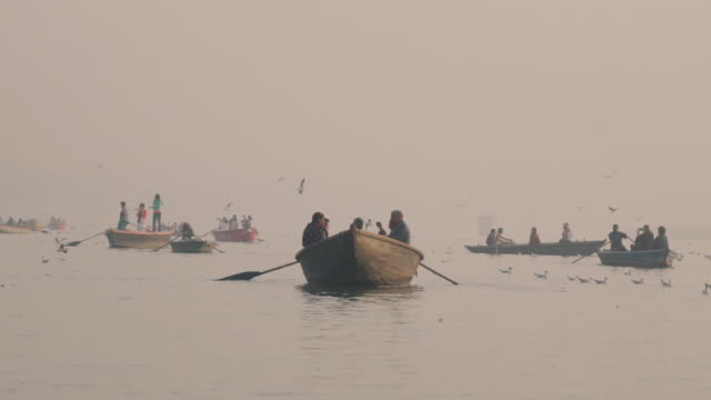 people sit in boats at the ganges river at sunrise - slow motion - smog stock videos & royalty-free footage