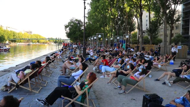 """people sit in chairs as they watch the film during paris plages launch of """"le cinema sur l'eau"""" with the screening of """"le grand bain"""" at bassin de la... - laziness stock videos & royalty-free footage"""