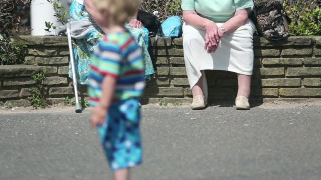 people sit on benches as an elderly woman is pushed past in a wheelchair in the sunshine in worthing uk on tuesday june 10 anonymous shot of two... - flat cap stock videos & royalty-free footage