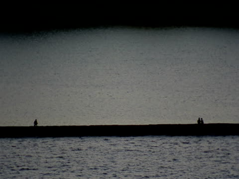 people sit on harbour wall as sea water ripples bombay - 姿勢をとる点の映像素材/bロール