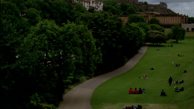 People sit on the lawn in Princes Street Gardens with Old Town and castle on hill in background.  Edinburgh, Scotland