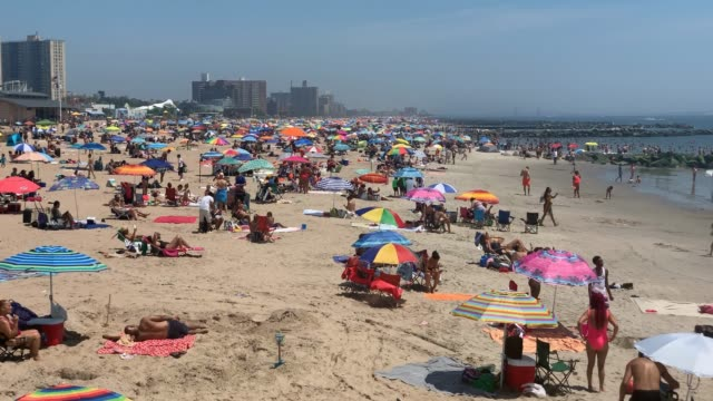 stockvideo's en b-roll-footage met people sit on the sand on the beach at coney island on july 19, 2020 in the brooklyn borough of new york city. much of the east coast is experiencing... - zwembroek