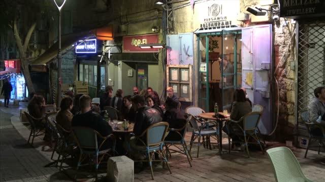 people sit outside a newly reopened restaurant on march 07, 2021 in jerusalem, israel. following israel's immunization campaign israeli cabinet eased... - israel bildbanksvideor och videomaterial från bakom kulisserna