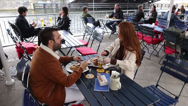 people sit outside at a restaurant along the spree river on the second day that berlin's restaurants were allowed to reopen for outdoor seating... - flowing water stock-videos und b-roll-filmmaterial