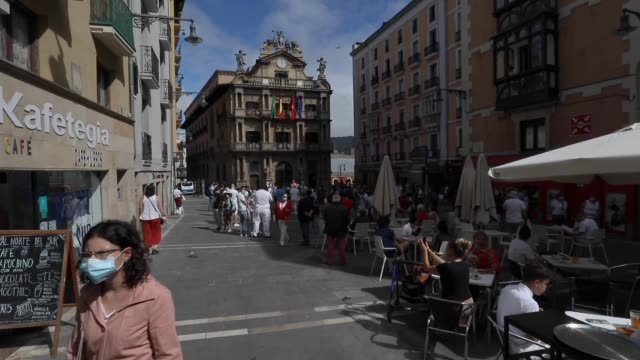 vídeos de stock e filmes b-roll de people sits in outdoor cafes in front of the ayuntamiento in consistorial square just past noon as the chupinazo commences the start of the cancelled... - meio dia