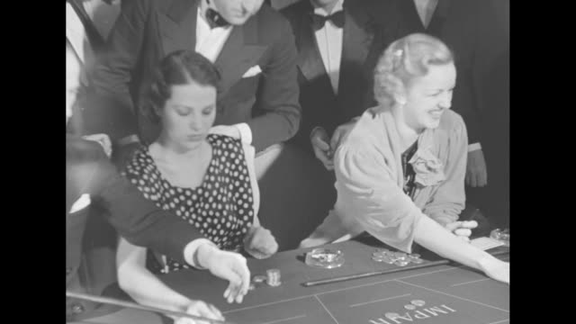 people sitting and standing around two roulette tables in casino playing roulette / close shot of two women sitting next to one another playing... - monaco stock videos and b-roll footage