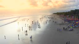 People sitting and walk on the beach and enjoying the party life in Seminyak Beach at sunset. 15 January 2020: Bali, Indonesia.