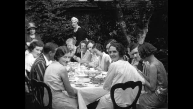 people sitting around a table in the garden eating dinner served by domestic staff - domestic staff stock videos & royalty-free footage