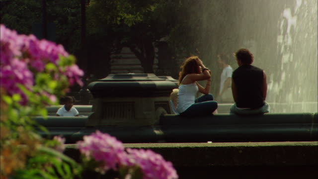 WS People sitting around and walking past fountain in Washington Square Park / Manhattan, New York, USA