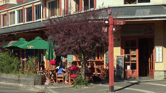 vidéos et rushes de ws people sitting at outdoor cafe table / pucon, cautin province, chile - façade
