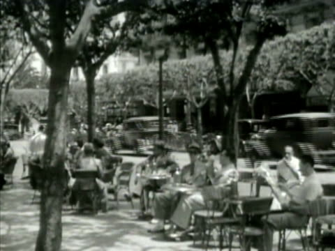 people sitting at outdoor street cafe tables ws people at tables ms pedestrians walking by tables bg ms people on street talking france occupied wwii... - アルジェリア点の映像素材/bロール