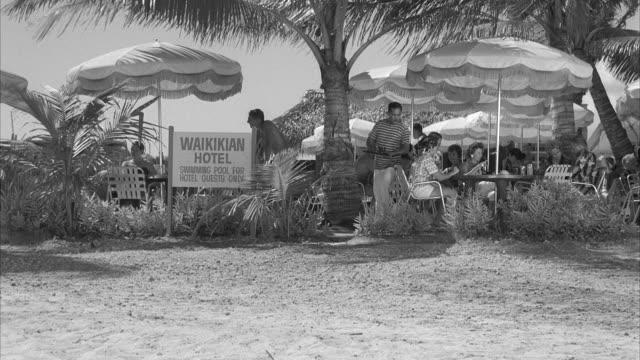 stockvideo's en b-roll-footage met  ms people sitting at tables on grounds of waikikian hotel at honolulu hawaii - 1959