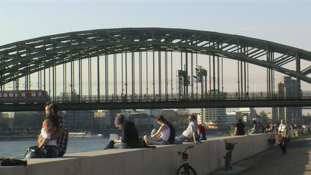 ws people sitting beside hohenzollern bridge looking out to rhine river / cologne, north rhine-westphalia, germany - rhein stock-videos und b-roll-filmmaterial