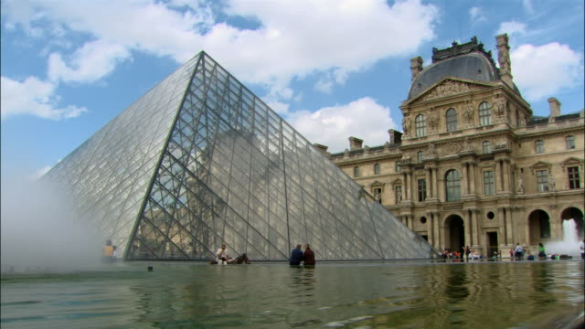 People sitting by reflecting pool at base of Louvre Pyramid / Paris, France