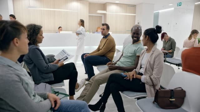 ds people sitting in a waiting room in a modern hospital - sala d'attesa video stock e b–roll